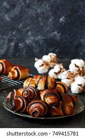 Rugelach with chocolate filling on plate on black background