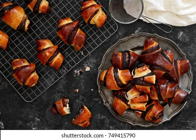 Rugelach with chocolate filling on plate on black background, top view