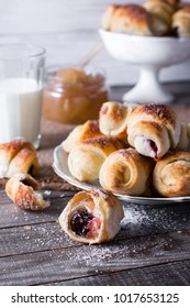 Rugelach with jam filling on plate with milk on wooden background - a traditional pastry