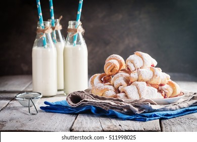 Rugelach with jam filling on plate with milk on wooden background