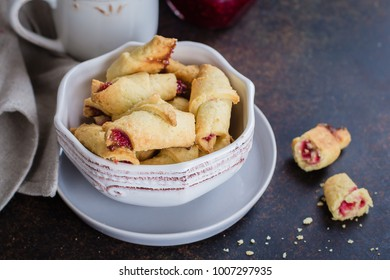 Rugelach (shortbread cookies) with jam filling on stone concrete table background. Copy space