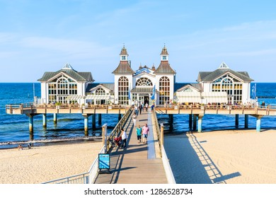 RUGEN ISLAND, GERMANY - MAY 28, 2018: Wooden pier on sandy beach and famous Sellin Seebruecke (Sellin Pier) in summer, Ostseebad Sellin tourist resort, Baltic Sea, Germany.