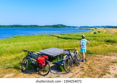 RUGEN ISLAND - MAY 31, 2018: Young woman cyclist resting with bicycle on route from Baabe to Moritzdorf village in countryside spring landscape, Ruegen island, Baltic Sea, Germany.