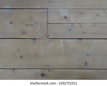 A rugged background of wooden floor boards with nails and dark areas of knots. Textured and brown, beige, cream.