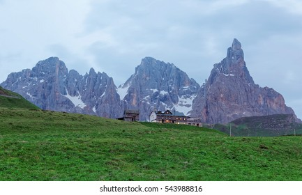 Rugged Cimon della Pala among peaks of Pale di San Martino mountains with a hotel on green grassy hill in Passo Rolle, Trentino Alto Adige, South Tyrol, Italy ~ Summer scenery of beautiful Dolomiti
