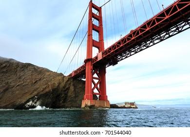Rugged cliffs at end of Golden Gate Bridge span splashed with waves