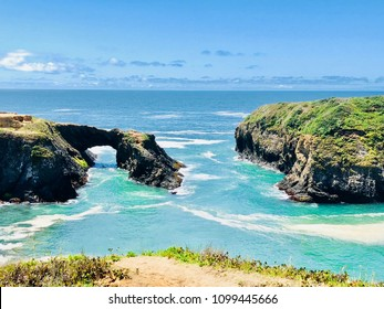 Rugged Coastline with Cliff Tunnel in Bay Beach Landscape