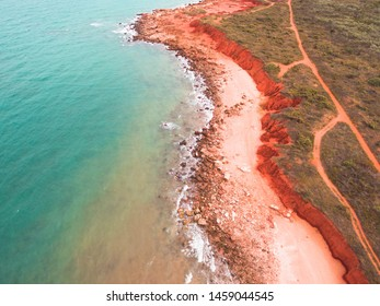 The rugged coastline of Reddell Beach in Broome, Western Australia as seen from the air with a drone. An outback road can be seen running parallel to the red cliffs, not far from the turquoise water.