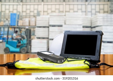 Rugged computers tablet and Bluetooth barcode scanner in front of modern warehouse