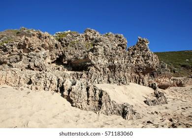 Rugged and dramatic rocks on a beach near the sea.