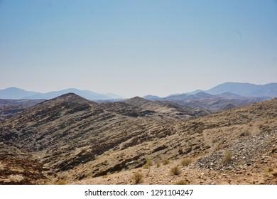Rugged granite hills beside a rough gravel road, Damaraland, Namibia, Africa.