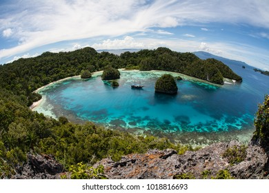 """Rugged limestone islands surround a beautiful, tropical lagoon in Raja Ampat, Indonesia. This remote region is called the """"heart of the Coral Triangle"""" due to its extraordinary marine biodiversity."""