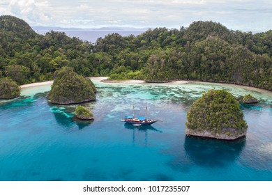 "Rugged limestone islands surround a ship and a beautiful lagoon in Raja Ampat, Indonesia. This remote region is called the ""heart of the Coral Triangle"" due to its extraordinary marine biodiversity."
