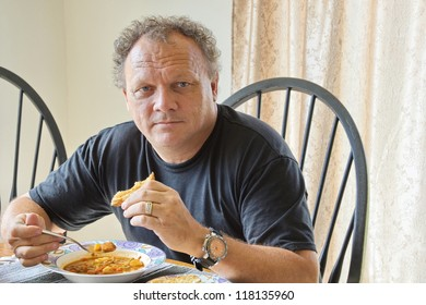 A rugged looking, mature male eating a bowl of healthy vegetable beef soup and bread at a table, looking candidly toward the camera.