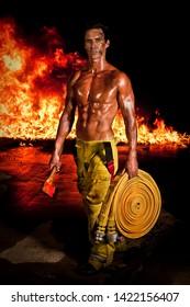 Ein robuster und muskulöser Feuerwehrmann mit einer Axt und einem Feuerschlauch in Händen und wütendem Feuer im Hintergrund. Fireman-Kalender.