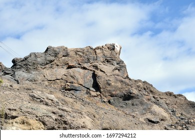 Rugged Outcrop of Volcanic Rock against Blue Sky with White Clouds