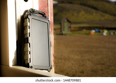 Rugged power bank battery with solar cell charging in the sun, nature and tents of campsite in the background