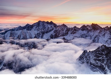 Rugged snow covered mountains rising up above thick clouds at sunrise, High Tatras, Slovakia