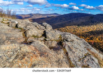 Rugged stone guards the distant view of fall colors in the Brandon Gap of Vermont.