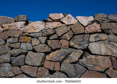 Rugged stone wall against the blue sky