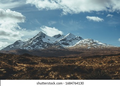 Rugged terrain with snowcapped mountains on the background on the Isle of Skye on the north of Scotland on a sunny spring day