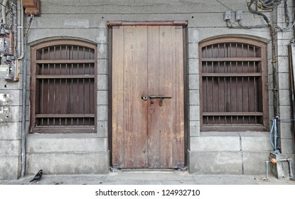 A rugged vintage timber door on a colonial architectural godown building.