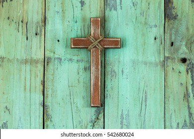 Rugged wood cross with rope hanging on antique rustic mint green wooden background; Christmas and Easter holiday background with painted copy space