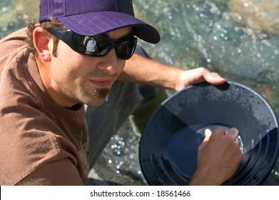 Rugged young man gold panning at a creek.