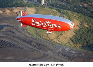 RUHR DISTRICT / GERMANY LATE 1990s WDL Airship 1B, D-LDFQ, cn 01 flying over the the Ruhr District, passing a coal stock. Used to advertise for several Companies like Koenig Pilsner Beer or Fuji Film.