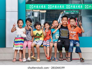 RUILI-CHINA-JUNE 28, 2014. Cheerful kids in front of a shop. Ruili is on the border with Myanmar, 64% of population are members of five ethnic minorities including Dai, Jingpo, Deang, Lisu, Achang.