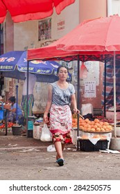 RUILI-CHINA-JUNE 28, 2014. Traditional dressed woman on a market. Ruili is on the border with Myanmar, 64% of population are members of five ethnic minorities like Dai, Jingpo, Deang, Lisu, Achang.