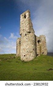 Ruin of ancient Scottish castle with green grass in front and blue cloudy sky in the background, vertical