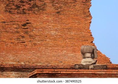 Ruin Buddha statue in front of brick wall, Wat Mahatat, Ayutthaya Historical Park, Ayutthaya, Thailand
