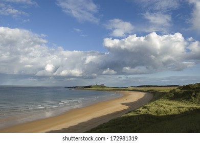 The ruin of Dunstanburgh Castle in the distance beyond the sands of Embleton Bay