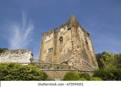 Ruin of a medieval castle on top of a hill in Guildford Surrey. Seen here on a clear summers day with a strange ghost like cloud filling a blue sky.