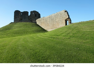 Ruin of medieval fortress sitting on grassy hill