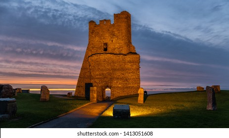 A ruin on the shore to the Irish Sea in the Welsh coastal town of Aberystwyth in the evening after sunset. The scene is lit up by many lamps.