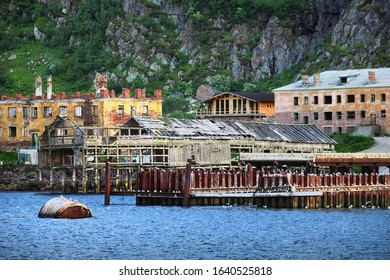 Ruined abandoned buildings, houses, dock and old rusty barrel in calm blue water of Barents sea at the background of sheer cliff in Teriberka settlement, Murmansk district, Kola peninsula, Russia