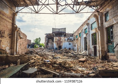 Ruined abandoned industrial building with large pills of concrete garbage, aftermath of natural disaster, hurricane, earthquake or war, toned