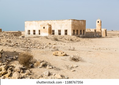 Ruined ancient old Arab pearling and fishing town Al Jumail, Qatar. The desert at coast of Persian Gulf. Abandoned mosque with minaret. Deserted village. Pile of stones