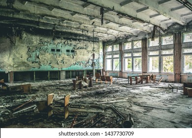 ruined assembly hall with debris and overturned chairs in abandoned Pripyat school. Chernobyl Soviet Union