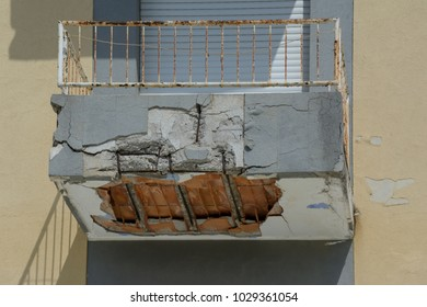 ruined balcony that is about to collapse with visible construction steel and bricks