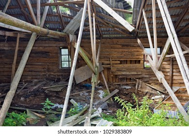 Ruined broken wooden rural barn shed - inside view. Sunny summer August day outdoor shot