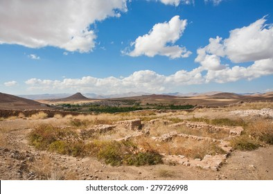 Ruined city in beautiful valley in the Middle East with low mountains in the distance under the white clouds on a sunny day