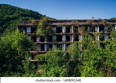 Ruined overgrown apartment house with bullet marks in ghost mining town, consequences of war in Abkhazia, green post-apocalyptic concept.