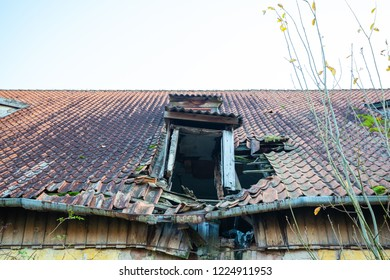 ruined sagging tiled roof of an old house