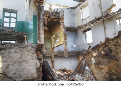 Ruined school inside with fallen floors and holes in the walls