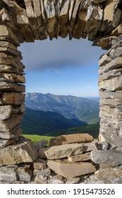 Ruiniertes Steinbogenfenster mit Blick auf die malerische Landschaft der Ligurischen Berge in Italien