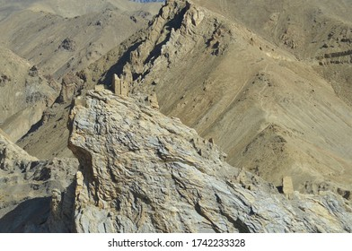 Ruined towers of a stone building remain on the edge of a cliff in Ladakh, India. Another tower lower down the slope. The cliff is part of a barren mountain range.