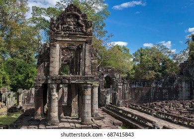 Ruined two-storied building with carved bas-relief and round columns in ancient Khmer complex Preah Khan, Angkor Wat, Siem Reap, Cambodia